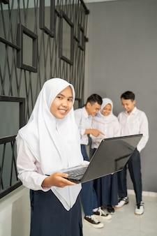 ノートパソコンを使用している間、ベールと制服を着たアジアのティーンエイジャーがカメラに微笑んだ