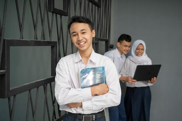 制服を着たアジアのティーンエイジャーが本を抱きしめながらカメラに微笑む