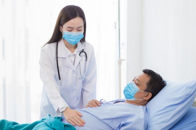 アジアの女性医師が、病院で安静になっている男性患者の症状をチェックしています。どちらもコロナウイルス病を保護するためにサージカルマスクを着用しています(covid19)。