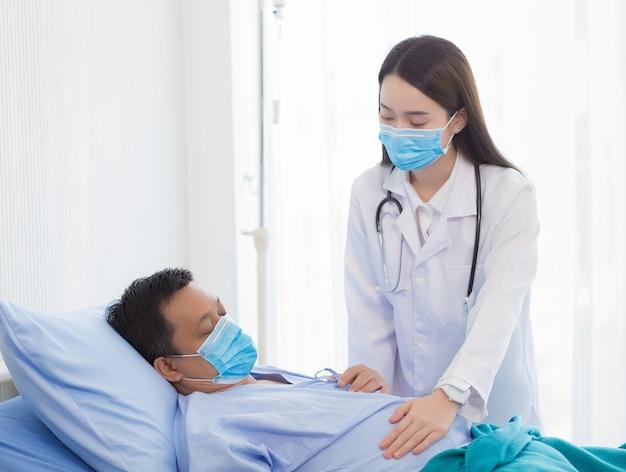 아시아 여성 의사가 병원에서 침대에 누워 있는 남성 환자의 증상을 확인하고 있다