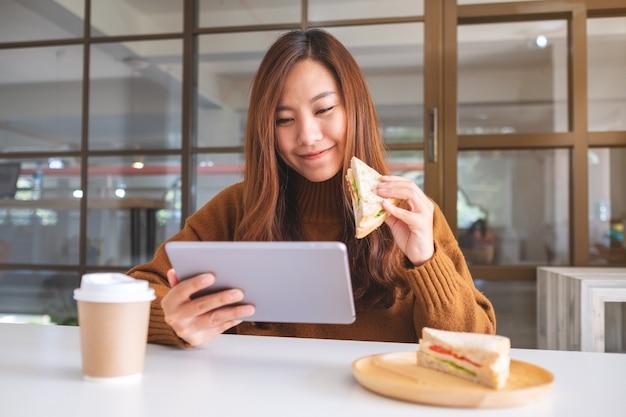 Азиатская женщина держит и ест сэндвич из цельной пшеницы во время использования планшетного пк