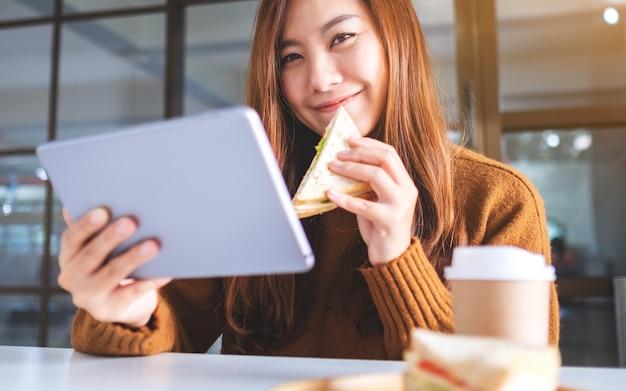 タブレットpcを使用しながら全粒小麦のサンドイッチを持って食べているアジアの女性