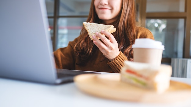 Азиатская женщина держит и ест бутерброд из цельной пшеницы во время работы на портативном компьютере
