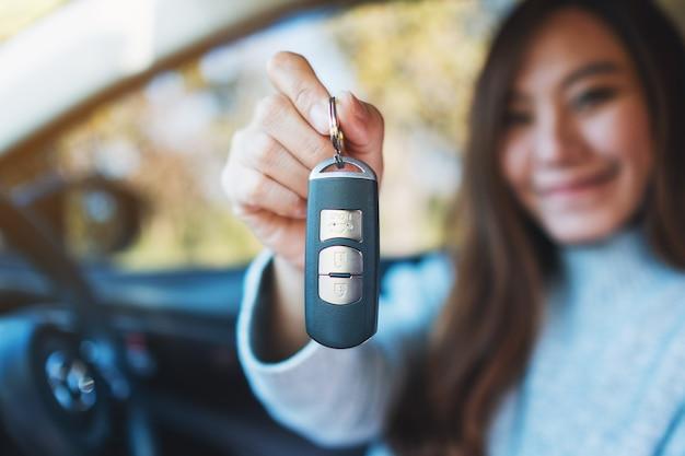 Азиатская женщина, держащая ключ от машины, сидя в машине