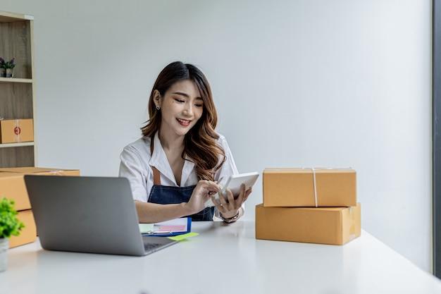 アジアの女性が白い計算機を押しています。彼女はオンラインストアを所有しており、注文金額計算機を使用して、顧客が支払わなければならない金額の概要を取得しています。オンライン販売のコンセプト。