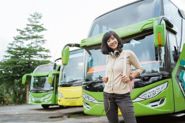 아시아 여자는 배낭과 버스의 배경에 웃고 헤드폰에 서있다