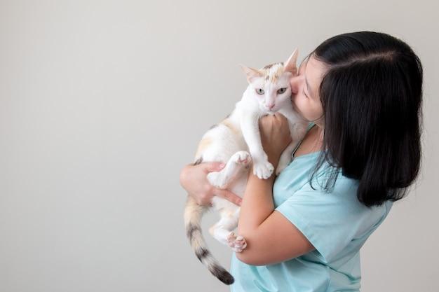 Азиатская женщина нежно держит кошку и целует ее.