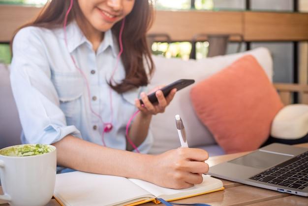 座っている、電話を持っている、音楽を聴いている、そして喫茶店での仕事を書き留めているアジア人女性がリラックスしました。