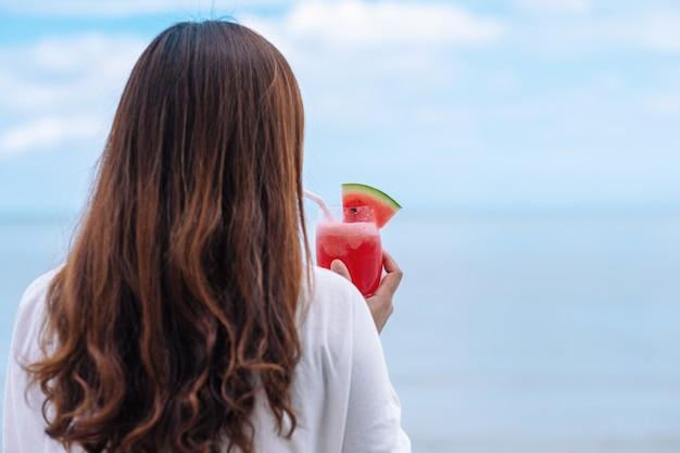 海のそばでスイカジュースを飲みながら後ろに立っているアジアの女性