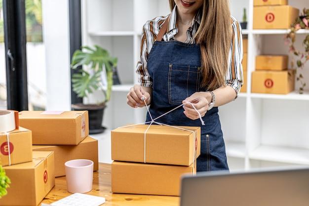 고객의 상자에 소포를 묶는 아시아 여성인 그녀는 온라인 상점을 소유하고 있으며 개인 운송 회사를 통해 포장하고 배송합니다. 온라인 판매 및 온라인 쇼핑 개념입니다.