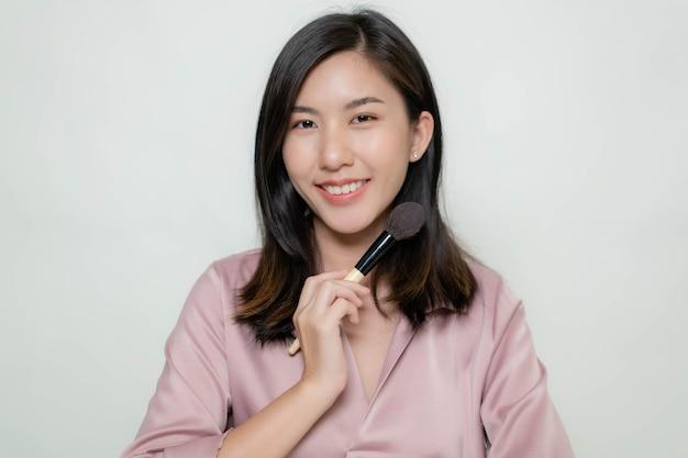 チークブラシを使用しているアジアの女性