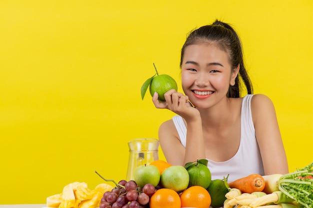 Азиатская женщина в белой майке. удерживаю апельсин правой рукой и на столе много разных фруктов.