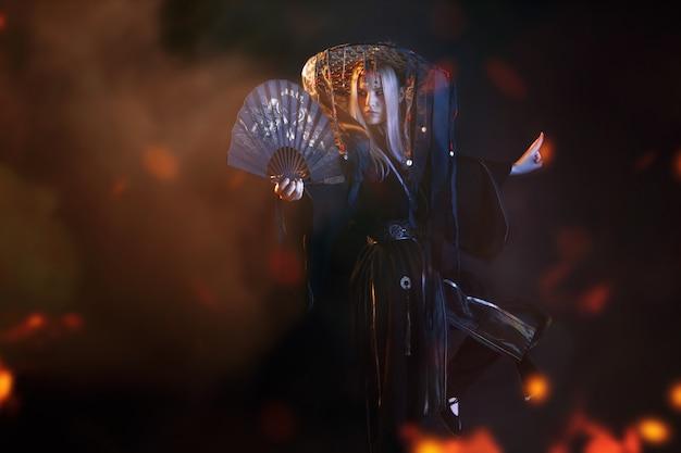 Азиатский персонаж в кимоно и соломенной шляпе с лентами среди огня