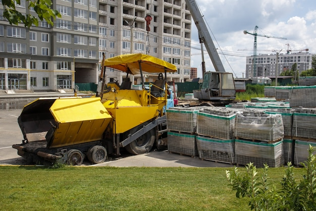 建設現場にアスファルト舗装が駐車されています。道路建設機械は倉庫の道路のそばに立っています。重い道路の建設と街路の修理。