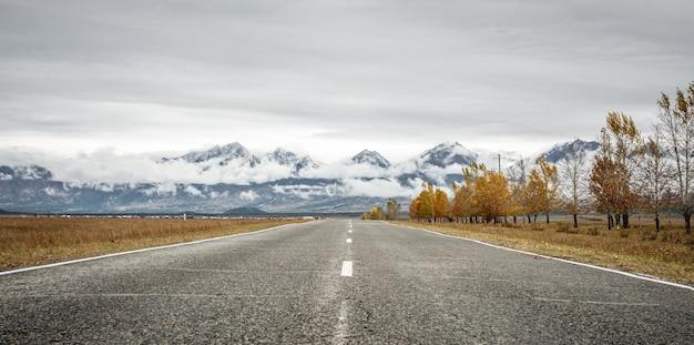 아스팔트 도로, 노란 잎, 산, 구름이 있는 숲. 아름다운 가을 풍경
