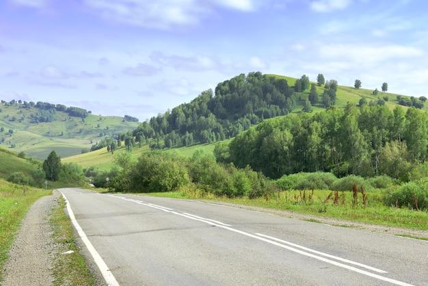 Асфальтированная дорога в окружении гор, заросших деревьями и травой под голубым облачным небом. сибирь, россия