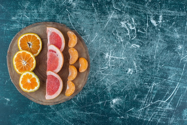 青い背景の上のボード上の柑橘系の果物のスライスの品揃え。高品質の写真