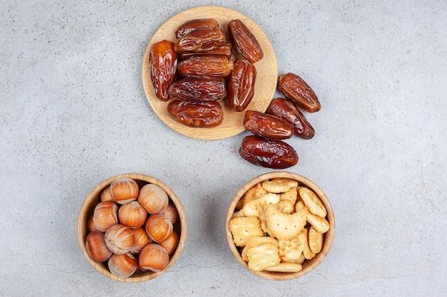 Ассортимент фиников на деревянной доске и орехов и печенья в мисках на мраморном фоне. фото высокого качества