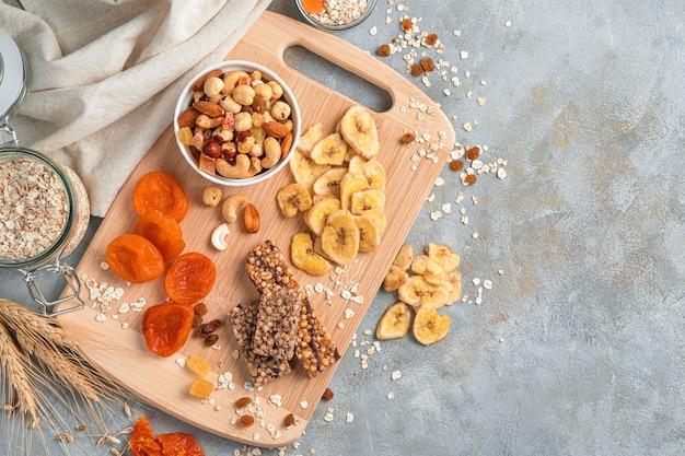 Ассортимент сухофруктов, орехов, батончиков мюсли и хлопьев на серой стене с местом для копирования. натуральные полезные закуски.