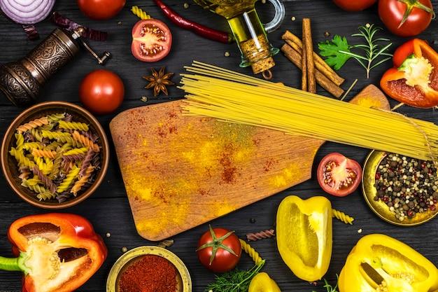 黒いキッチンの表面に新鮮な野菜やスパイス、オリーブオイル、まな板、パスタの品揃え。テキスト用のスペース。