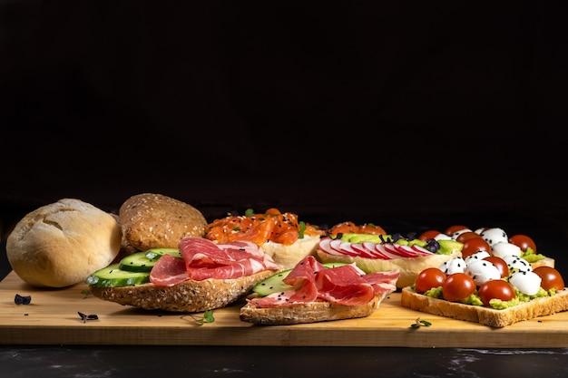 魚、チーズ、肉、野菜のサンドイッチの品揃えがボードとパンの上に置かれました