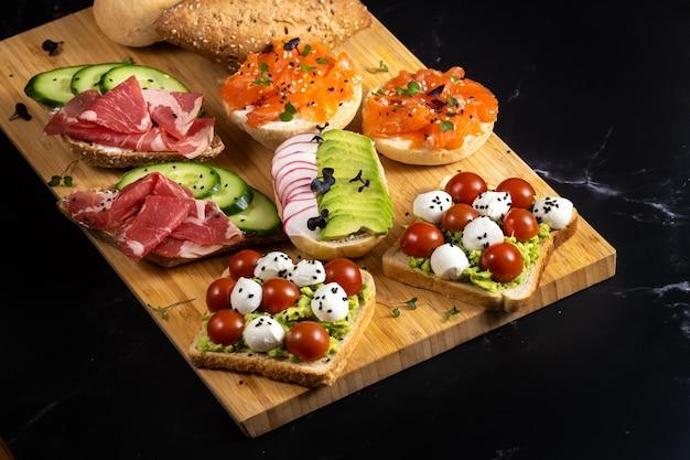 魚、チーズ、肉、野菜のサンドイッチの品揃えがボードとパンの上に置かれました。