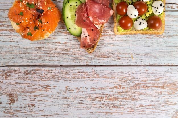 木製のテーブルの上に魚、チーズ、肉、野菜のサンドイッチの品揃えが置かれています