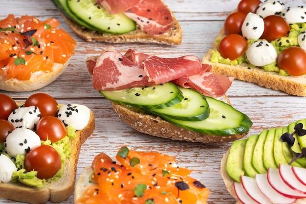 На деревянном столе лежал ассортимент бутербродов с рыбой, сыром, мясом и овощами.