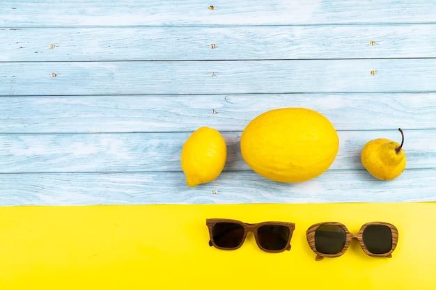 黄色の果物とグラスの品揃えは、青い木製の背景と黄色の背景の上にあります