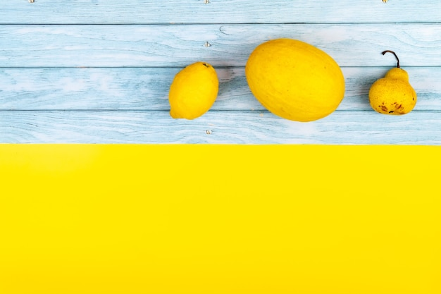 黄色い果物の品揃えは、青い木製の背景と黄色の背景にあります。