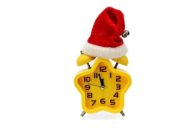 Рождественские часы со звездочкой показывают оставшееся время до полуночи в шляпе санта-клауса на белом фоне. желтый 12, двенадцать часов