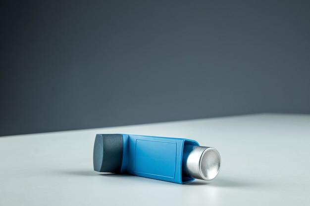 喘息吸入器は、灰色の背景に白いテーブルの上に横たわり、喘息発作を起こします。気管支喘息、咳、アレルギー、呼吸困難の治療の概念。