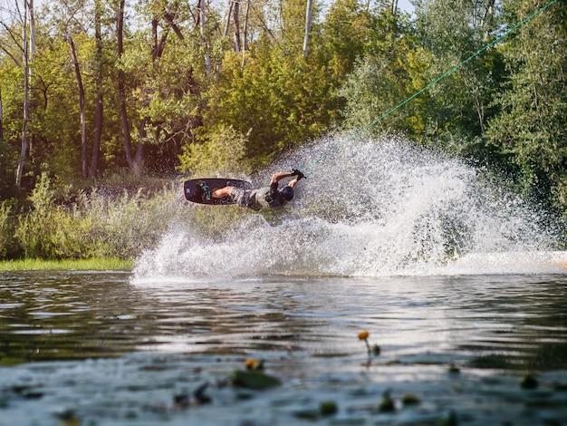 アスリートが水しぶきでウェイクボードトリックを実行します