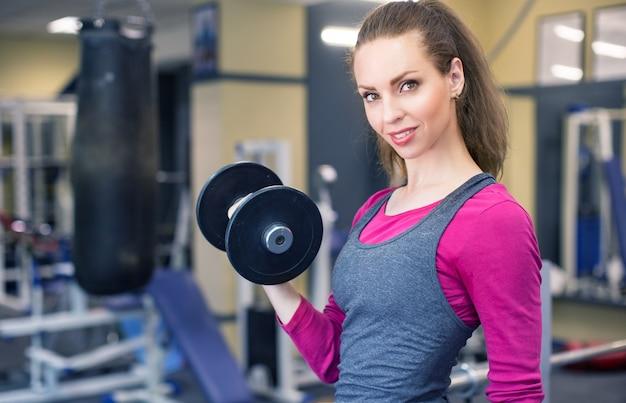 운동 선수 웃는 여자는 체육관에서 아령을 당긴 다.