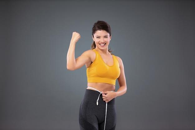 테이프로 그녀의 허리를 측정하는 회색 벽 앞의 운동복에 운동 맞는 여자