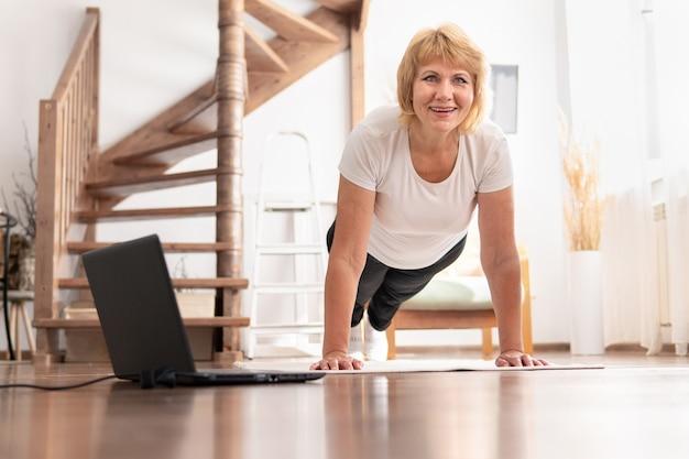魅力的で幸せな中年女性が明るい部屋で体操やフィットネスをする