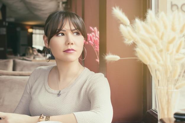 매력적인 아시아 여성이 카페에서 누군가를 기다리고 있습니다.
