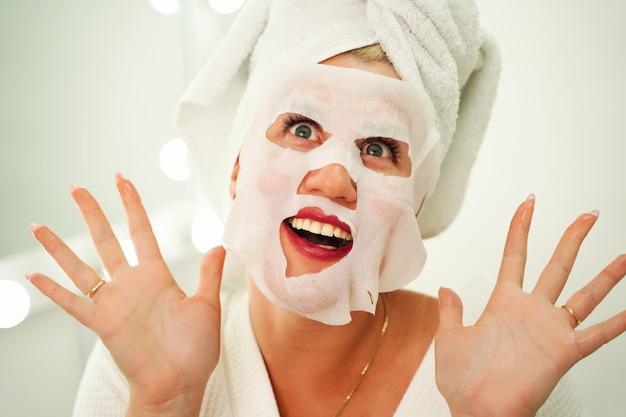 Привлекательная красивая девушка с полотенцем на голове ухаживает за лицом с тканевой маской на лице е ...