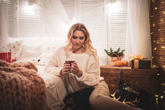 お茶とニットのセーターを着た魅力的な金髪の女性がベッドに座っています。涼しい天候の窓でお茶。一人で冬の夜。温かい飲み物で暖められたクリスマスイブの孤独な少女