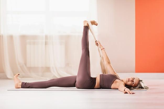 운동복을 입은 매력적인 금발의 여성이 다리 근육을 스트레칭하기 위해 요가 스트랩으로 등을 대고 누워 pada supta padaangushhtasana 운동을 수행합니다.