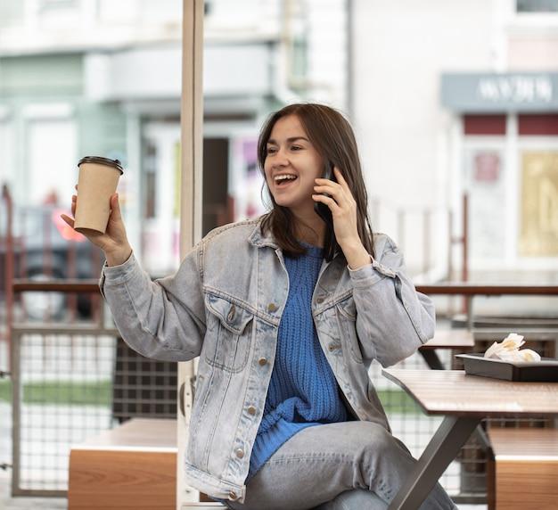 カジュアルなスタイルが魅力的な女の子が、サマーテラスでコーヒーを飲みながら電話で話している。