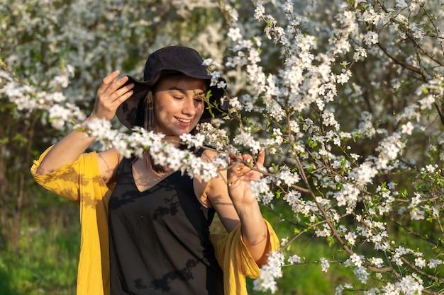 피는 나무들 사이에서 모자를 쓴 매력적인 소녀가 봄 꽃의 향기를 즐깁니다.