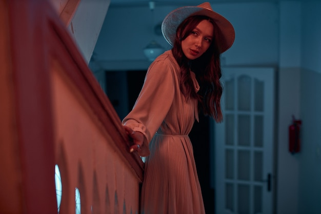 모자를 쓴 매력적인 소녀가 나무 계단 근처에 서서 오래된 집 고품질 사진에서 창의적인 사진 촬영을 옆으로 바라보고 있습니다.