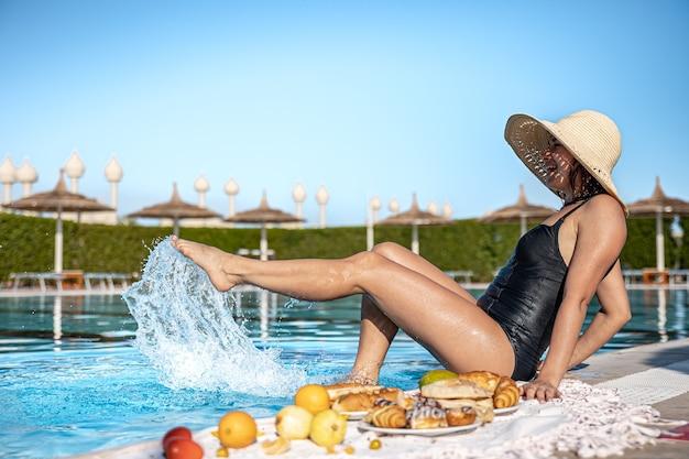 매력적인 소녀가 수영장 근처에 앉아 아침 식사를 즐기고 있습니다. 따뜻한 나라에서 휴식과 휴가의 개념.