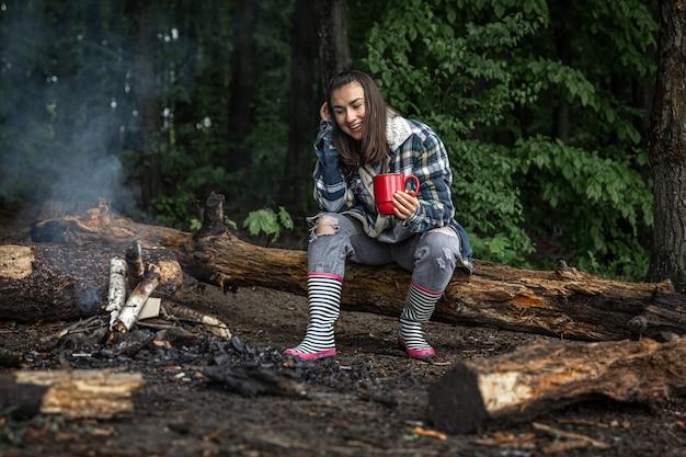 手にカップを持った魅力的な女の子が丸太の上に座って、森の火のそばで体を温めます。