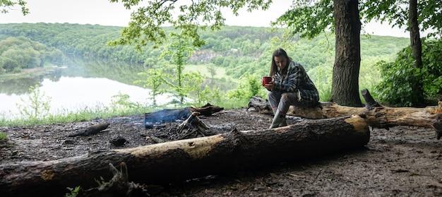 Симпатичная девушка с чашкой в руке сидит на бревне и греется у костра в лесу.