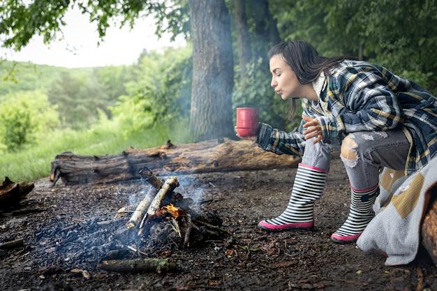 カップを手にした魅力的な女の子が森の火のそばで暖まります。