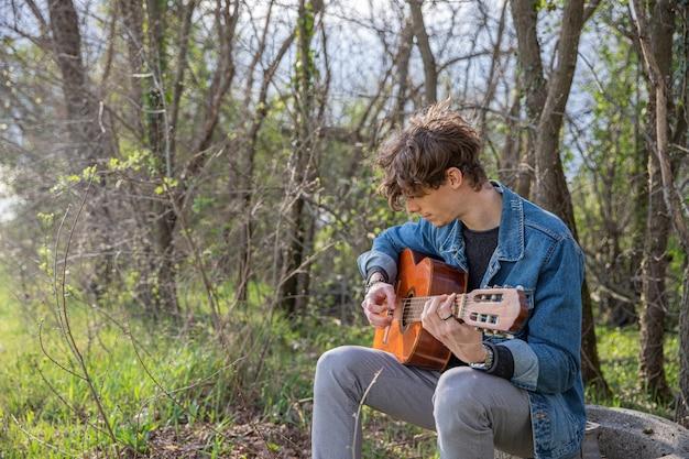 魅力的な男が森でギターを弾く。