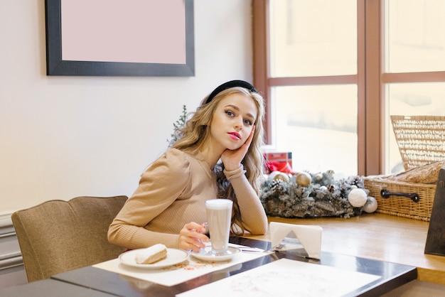 매력적인 행복한 소녀가 크리스마스로 장식된 카페에 앉아 커피를 마시고 디저트를 먹고 있다