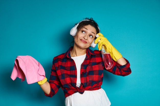魅力的な主婦、洗剤とクリーニングアクセサリーで青に立ち、思慮深い視線で見上げる